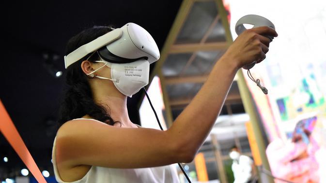 Seorang wanita mencoba kacamata virtual reality di stan Orange selama pameran Mobile World Congress (MWC) di Barcelona (28/6/2021). (AFP/Pau Barrena)