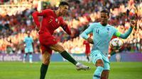 Bintang Timnas Portugal, Cristiano Ronaldo (kiri), berduel dengan bek Timnas Belanda, Virgil van Dijk, pada final UEFA Nation League, di Stadion Dragao, Portugal, Sabtu (9/6/2019). (AFP/Gabriel Bouys)