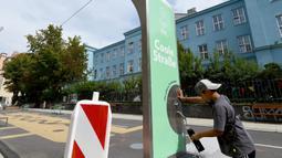 "Seorang anak mengambil air minum di ""jalan sejuk"" yang disediakan di Waltergasse, Wina, 20 Juli 2020. Wina menyediakan 22 ""jalan sejuk"" untuk yang ingin menyejukkan diri, lengkap dengan berbagai fasilitas seperti mainan, alat olahraga dan air bersih gratis hingga 20 September 2020. (Xinhua/Guo Chen)"