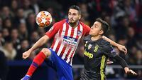 Gelandang Atletico Madrid, Koke, duel melawan Paulo Dybala dalam leg pertama Liga Champions 2018-2019 di Wanda Metropolitano Stadium (20/2/2019). (AFP/Gabriel Bouys)