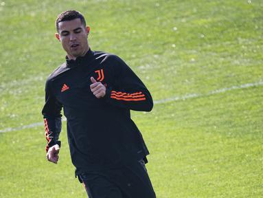 Penyerang Juventus, Cristiano Ronaldo melakukan pemanasan saat menghadiri sesi latihan tim di pusat pelatihan Juventus di Turin (8/3/2021). Ronaldo dan rekan-rekannya akan bertanding melawan Porto pada leg kedua babak 16 besar Liga Champions di Allianz Stadium. (AFP/MARCO BERTORELLO)