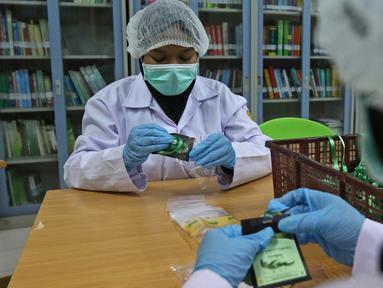 Pekerja lab mengemas serbuk hasil pengolahan laboratorium nano teknologi di balai penelitian dan pengembangan Kementan, Bogor, Jawa Barat, Selasa (7/7/2020). Balai penelitian ini melakukan penelitian terhadap Eucalyptus sebagai pencegah virus dalam jenis kategori jamu. (Liputan6.com/Herman Zakharia)