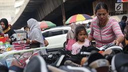 Seorang ibu bersama anaknya memilih sepatu di Pasar Asemka, Jakarta, Selasa (7/9/2019). Jelang dimulainya tahun ajaran baru, Pasar Asemka ramai dikunjungi warga untuk berbelanja keperluan sekolah. (Liputan6.com/Helmi Fithriansyah)