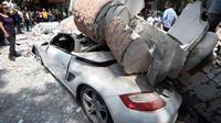 Bangunan yang menghantam sebuah mobil setelah gempa mengguncang Kota Meksiko (19/9). Sekitar 100 orang tewas dalam bencana gempa bumi 7,1 Skala Richter tersebut. (AFP Photo/Alfredo Estrella)