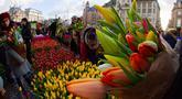Orang-orang memetik tulip gratis pada Hari Bunga Tulip Nasional di Dam Square yang berada di seberang Royal Palace, Amsterdam, 18 Januari 2020. Hari Bunga Tulip Nasional ini menandai pembukaan musim bunga tulip untuk industri bunga Belanda.  (AP Photo/Peter Dejong)