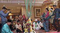 Aktris Ayu Dewi menggendong anak keduanya Mohamad Aqlan Ukasyah Datau, didampingi suami Regi Datau saat prosesi Mohuntingo di kawasan Tebet, Jakarta, Minggu (27/08). (Liputan6.com/Herman Zakharia)