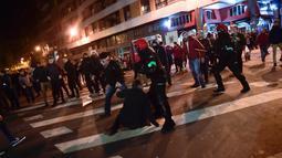 Polisi bentrok dengan suporter Athletic Bilbao dan Spartak Moskow di Stadion San Mames, Bilbao, Spanyol, Kamis (22/2). Seorang polisi tewas setelah mencoba membubarkan bentrok suporter Athletic Bilbao dan Spartak Moskow. (AP Photo/Alvaro Barrientos)