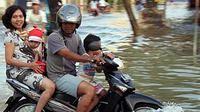 Seorang pengendara motor bersama keluarga melewati genangan banjir, di Kabupaten Sampang, Madura, Jatim.(Antara)