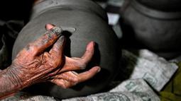 Seorang pembuat tembikar membuat pot tanah liat menggunakan tangan dalam bengkel rumah di Banda Aceh, Aceh, Rabu (4/8/2021). (CHAIDEER MAHYUDDIN/AFP)