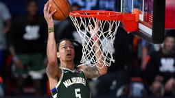 Pebasket Milwaukee Bucks, D.J. Wilson, memasukkan bola saat melawan Washington Wizards pada laga NBA, Selasa (11/8/2020). Bucks mengalahkan Wizards dengan skor 126-113. (AP Photo/Ashley Landis, Pool)
