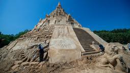 """Pemahat beraktivitas di istana pasir tertinggi pada kompetisi tahunan """"Sand Sculptures Festival"""" di Binz, Pulau Reugen di Laut Baltik, Jerman, 5 Juni 2019. Istana pasir itu berhasil memecahkan rekor sebagai istana pasir tertinggi di dunia dengan rincian ketinggian 17,66 meter. (Jens Büttner/dpa/AFP)"""