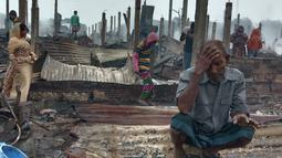 Seorang pengungsi Rohingya yang tampak sedih melihat tempat tinggalnya ludes terbakar saat musibah kebakaran melanda kamp pengungsi Nayapara di Cox's Bazar, Bangladesh (14/1/2021). Tidak ada laporan korban jiwa akibat kebakaran ini. (AP Photo/Mohammed Faisal)