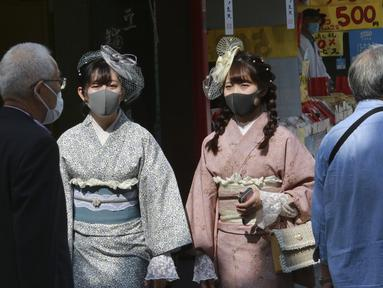 Pengunjung berpakaian kimono yang mengenakan masker untuk melindungi diri dari penyebaran virus corona berjalan-jalan di distrik perbelanjaan Asakusa di Tokyo, Jepang, Rabu (14/10/2020). Tokyo mengonfirmasi lebih dari 170 kasus virus corona baru pada hari Rabu. (AP Photo/Koji Sasahara)