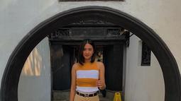 Saat berlibur, wanita kelahiran 15 Oktober 1997 ini sering tampil dengan gaya kasual. Kali ini ia tampil kece dengan atasan motif garis-garis berwarna kuning mustard dan putih. Celana yang dikenakannya pun senada dengan warna bajunya. (Liputan6.com/IG/@nadyaarina)