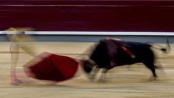 Dalam foto yang diambil dengan kecepatan rana lambat ini, matador Emilio de Justo saat adu banteng di arena adu banteng Las Ventas, Madrid, Spanyol, Minggu (4/7/2021). Adu banteng ini berlangsung di tengah pandemi virus corona COVID-19. (AP Photo/Manu Fernandez)