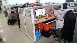 Pekerja berlindung di bawah meja saat simulasi bencana di Gedung Graha BNPB, Jakarta, Kamis (26/4). Disimulasikan telah terjadi gempa 7,5 skala Richter di pesisir selatan Pulau Jawa. (Liputan6.com/Arya Manggala)