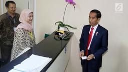 Presiden Jokowi saat meninjau Ruang Pelayanan Terpadu di Kementerian Luar Negeri, Jakarta, Senin (12/2). Selain untuk kekonsuleran, Ruang Pelayanan Terpadu juga ada fasilitas diplomatik serta informasi dan media. (Liputan6.com/Angga Yuniar)