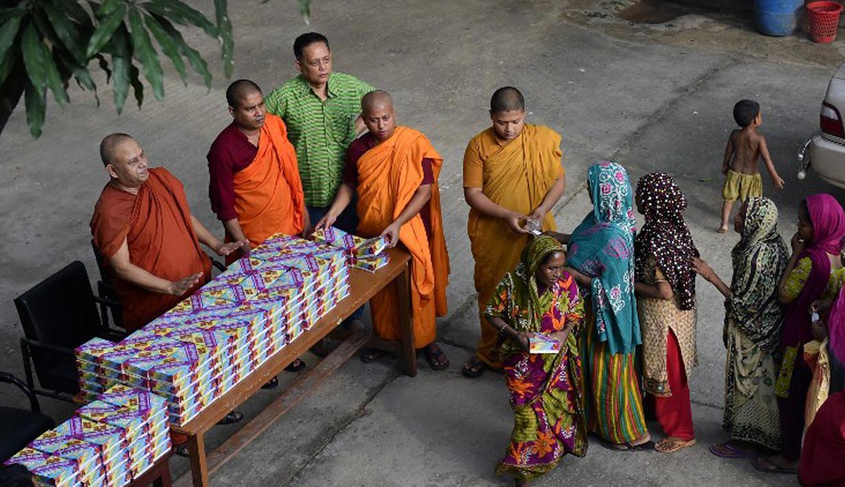 Sejumlah biksu membagikan iftar (makanan berbuka puasa) bagi umat muslim di Wihara Dhammarajika, Dhaka, Bangladesh, Selasa (7/7). Ini merupakan momen langka keharmonisan umat beragama di negara Asia. (AFP PHOTO/Munir uz ZAMAN)