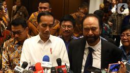 Presiden Joko Widodo atau Jokowi (kiri) didampingi Ketua Umum Partai Nasdem Surya Paloh (kanan) memberi keterangan saat menghadiri perayaan ulang tahun ke-8 Partai Nasdem di JIExpo, Jakarta, Senin (11/11/2019). Surya Paloh menyambut langsung kedatangan Jokowi di HUT Nasdem. (Liputan6.com/Angga Yunia