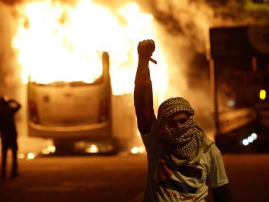 Seorang demonstran berada di dekat bus yang dibakar saat bentrokan dengan polisi dalam unjuk rasa di de Janeiro, Brasil, (29/4). Mereka menentang usulan perubahan undang-undang ketenagakerjaan dan sistem pensiun. (AP Photo/Leo Correa)