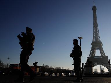 Polisi anti huru-hara berpatroli di dekat Menara Eiffel di Paris,  Senin (30/12/2019). Pemerintah Prancis akan mengerahkan 100.000 petugas polisi untuk mengamankan ruang publik pada perayaan malam Tahun Baru di tengah aksi mogok yang sedang berlangsung. (AP/Christophe Ena)