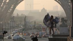 Model seksi ini bergaya di depan menara Eiffel saat matahari terbit dalam sesi pemotretan, Paris (11/3/2016). (AFP/Ludovic MARIN)