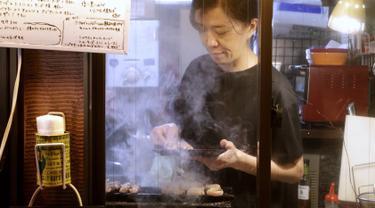 Seorang pemilik bar menyiapkan Yakitori di area jalan malam belakang pusat kota Tokyo (4/10/2019). Yakitori merupakan sate khas dari Jepang yang umumnya menggunakan daging ayam.  (AP Photo/Mark Baker)