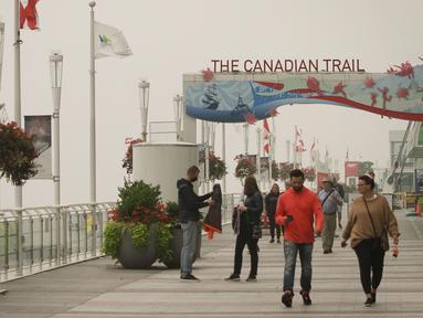 Sejumlah orang berjalan di pelabuhan yang diselimuti kabut asap tebal, Vancouver, British Columbia, Kanada, 13 September 2020. Kabut asap kebakaran hutan AS yang terus tertiup ke Vancouver menyebabkan kota tersebut masuk dalam lima kota dengan kualitas udara terburuk di dunia. (Xinhua/Liang Sen)