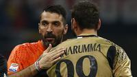 Kiper AC Milan Gianluigi Donnarumma berpelukan dengan kiper Juventus, Gianluigi Buffon usai pertandingan Liga Italia Serie A di stadion San Siro di Milan pada 22 Oktober 2016. (AFP Photo/Marco Bertorello)