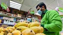Direktur Pelaksana Pakistan Supermarket Dubai Jhanzeb Yaseen memeriksa mangga sebelum pengiriman di Dubai, Uni Emirat Arab, Kamis (2/7/2020). Supermarket tersebut mengantarkan pesanan mangga untuk minimal pesanan sekitar USD 27. (CACACE GIUSEPPE/AFP)