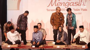 Wapres Jusuf Kalla (tengah) didampingi Ketua Himbara Maryono dan Menteri BUMN Rini M Soemarno dalam acara buka puasa bersama anak yatim di JCC, Jakarta, Kamis (15/06). Kegiatan ini mengundang 3.500 anak yatim.  (Liputan6.com/Fery Pradolo)