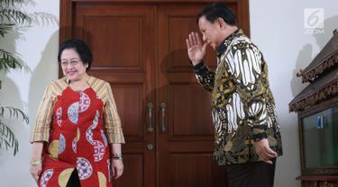 Ketua Umum Partai Gerindra, Prabowo Subianto (kanan) memberi hormat pada Ketua Umum PDIP, Megawati Soekarnoputri usai memberi keterangan terkait pertemuan dan makan siang bersama di kediaman Megawati di Jalan Teuku Umar, Jakarta, Rabu (24/7/2019). (Liputan6.com/Helmi Fithriansyah)