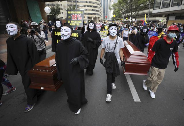 Para pengunjuk rasa membawa peti mati kosong selama pemogokan nasional untuk memprotes reformasi pajak yang diusulkan pemerintah, di ibu kota Kolombia, Bogota, pada Rabu (28/4/2021). (AP Photo/Fernando Vergara)