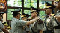 Kapolri Jenderal Tito Karnavian memasangkan tanda pangkat pada Irjen Mochamad Iriawan saat acara sertijab di Rupatama Mabes Polri, Rabu (26/7). Jabatan Iriawan sebagai Kapolda Metro Jaya digantikan oleh Irjen Idham Aziz. (Liputan6.com/Faizal Fanani)