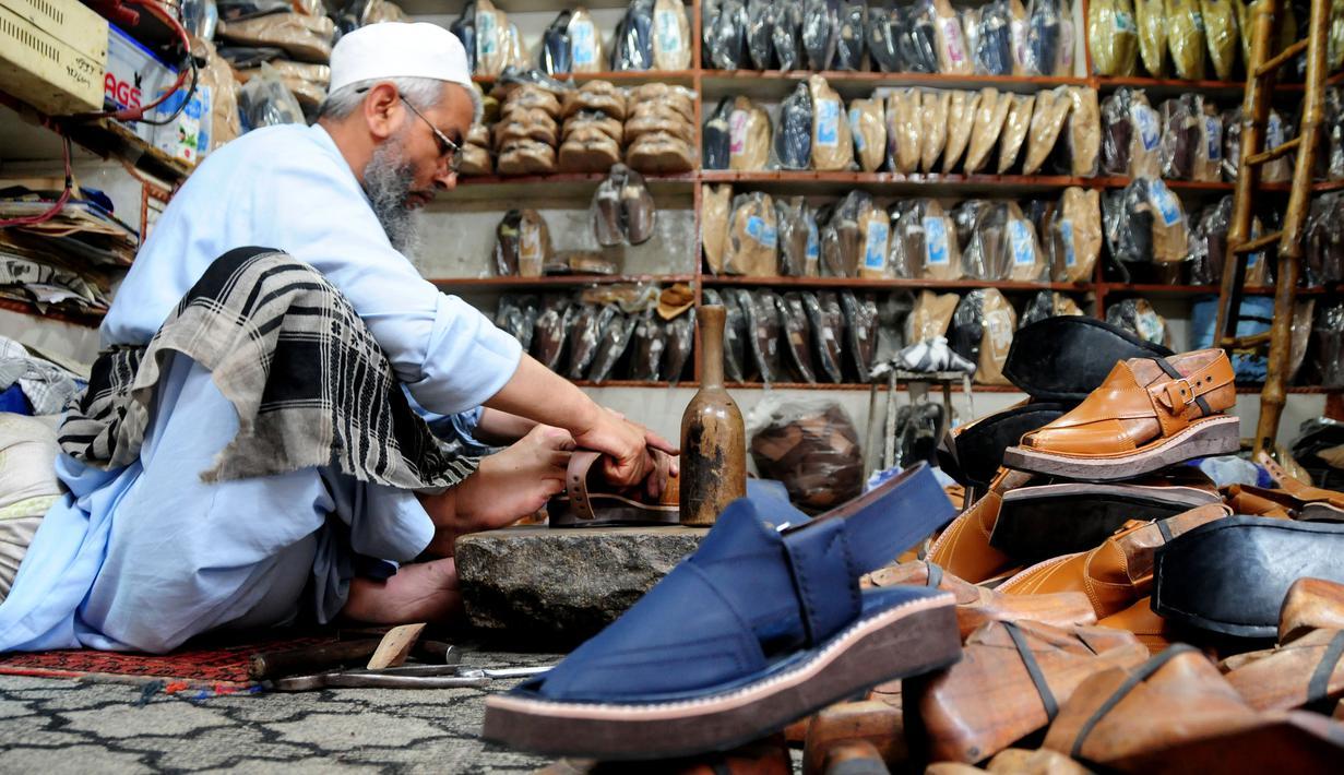 """Seorang pembuat sepatu asal Pakistan membuat sepatu tradisional yang dikenal sebagai """"chapli"""" di kalangan penduduk lokal untuk menyambut Hari Raya Idul Fitri di Peshawar, Pakistan barat laut, pada 19 Mei 2020. (Xinhua/Saeed Ahmad)"""