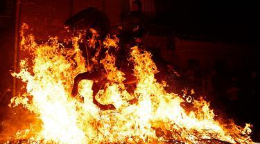 Seorang pria menunggangi kuda melewati api unggun saat festival Luminarias di San Bartolome de Pinares, Spanyol, Jumat (16/1/2020). Festival tersebut digelar setiap tahunnya, sehari sebelum perayaan Santo Antonius yang merupakan pelindung binatang. (AP Photo/Manu Fernandez)