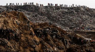 Sejumlah orang melihat proses evakuasi di lokasi longsoran sampah  di Tempat Pembuangan Akhir (TPA)  di Guatemala City, Guatemala, Rabu (27/4). Ribuan kubik sampah longsor dan menewaskan satu orang. (REUTERS/Josue Decavele)