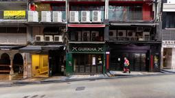 Seorang pengantar barang berjalan di jalan sepi di kawasan hiburan malam Lan Kwai Fong, Hong Kong (4/4/2020). ebijakan pemerintah Hong Kong itu membuat gemerlap hiburan malam di Lan Kwai Fong meredup seketika. (AFP/May James)