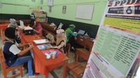 Guru memakai pelindung wajah melayani calon orang tua siswa yang mengalami kesulitan mendaftar secara online saat pendaftaran peserta didik baru (PPDB) tahun ajaran 2020/2021di SDN Pengadilan I Bogor, Jawa Barat, Selasa (9/6/2020). (merdeka.com/Arie Basuki)