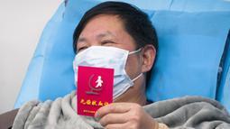 Pasien yang pulih dari coronavirus memegang sertifikat donor darah saat menyumbang plasma di Wuhan (17/2/2020). Pasien sembuh diimbau menyumbangkan plasma karena hasil awal mengindikasikan efektivitas produk terapeutik plasma konvalesen dalam mengobati pasien dengan kondisi kritis. (Xinhua/Cai Yang)