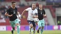 Striker Inggris, Harry Kane (tengah) berebut bola dengan bek Austria, Marco Friedl dalam laga uji coba menjelang berlangsungnya Euro 2020 di Riverside Stadium, Middlesbrough, Rabu (2/6/2021). Inggris menang 1-0 atas Austria. (AP/Scott Heppell/Pool)