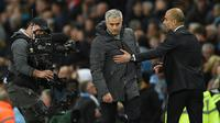 Pelatih Josep Guardiola berusaha merangkul pelatih Jose Mourinho selama pertandingan antara Manchester City melawan Manchester United di Liga Inggris di stadion Etihad, Inggris, (27/4). (AFP Photo/Oli Scarff)