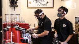 Pramusaji menggunakan pelindung wajah, masker dan sarung tangan saat menyajikan hidangan di The Atjeh Connection Coffee and Resto, Jakarta, Senin (8/6/2020). Tempat ini siap menerapkan protokol kesehatan dalam menerapkan tatanan kehidupan baru atau 'new normal'. (Liputan6.com/Faizal Fanani)