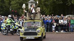 Rowan Atkinson, pemeran 'Mr Bean' membuat aksi lucu mengendarai mobil mini di atap mobil dan berkeliling di kawasan The Mall, London, Jumat (4/9/2015). Aksinya tersebut sebagai promosi serial TV dan Film komedi 'Mr Bean' (REUTERS / Toby Melville)