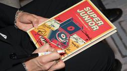 Tak hanya sekadar berfoto, member SuJu dan Presiden serta Iriana pun bertukar tanda tangan di album Replay. (Twitter/SJOfficial)