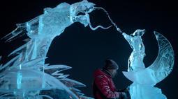 Seorang pemahat es memberikan sentuhan akhir pada patung es di festival Ice and Snow World Harbin, di Harbin, timur laut China, Jumat (3/1/2019). Festival es terbesar dunia ini diadakan untuk menyambut musim dingin yang berlangsung selama satu bulan lebih. (NOEL CELIS/AFP)