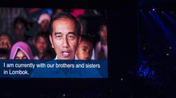 Presiden RI, Joko Widodo, memeberi Sambutan dari layar raksasa saat penutupan Asian Games di SUGBK, Jakarta, Minggu (2/9/2018). (Bola.com/Vitalis Yogi Trisna)