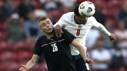 Gelandang Inggris, Jude Bellingham (kanan) berduel udara dengan striker Austria, Sasa Kaladzic dalam laga uji coba menjelang berlangsungnya Euro 2020 di Riverside Stadium, Middlesbrough, Rabu (2/6/2021). Inggris menang 1-0 atas Austria. (AP/Scott Heppell/Pool)