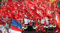 Sejumlah buruh membawa bendera berwarna merah saat aksi May Day 2016 di Jakarta, Minggu (1/5). Kaum buruh mengajukan tuntutan menolak upah murah serta pencabutan PP No. 78 Tahun 2015. (Liputan6.com/Angga Yuniar)