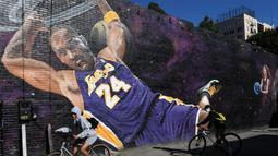 Pesepeda melintas di depan lukisan mural bintang LA Lakers, Kobe Bryant di Los Angeles, California, Selasa (26/1/2021). Lukisan dibuat untuk mengenang 1 tahun tragedi kecelakaan helikopter yang menewaskan Kobe Bryant bersama putrinya, Gianna. (Getty Images via AFP/Harry How)